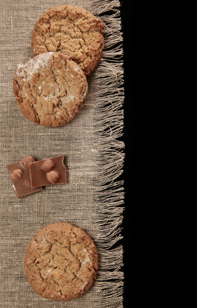 Photo for oat cookies and chocolate pieces on canvas tablecloth - Royalty Free Image