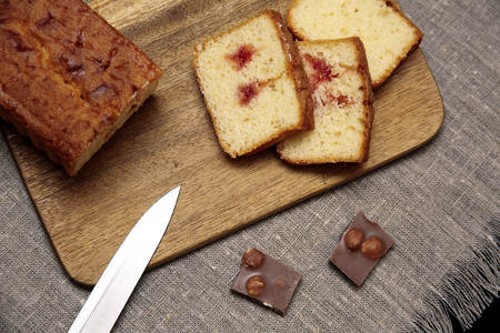 Photo for tasty cake on wooden cutting board and chocolate pieces on linen tableclothes - Royalty Free Image