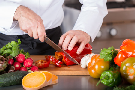 Foto de Chef cutting fresh and delicious vegetables for cooking - Imagen libre de derechos