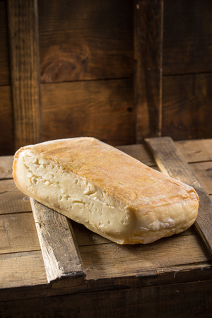Photo for Piece of taleggio cheese on wooden board on dark background. Studio shot - Royalty Free Image
