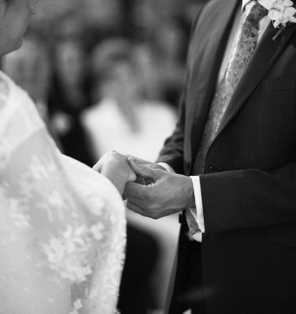 Black and white artistic digital rectangular horizontal photo of hand of bridegroom in dark long morning suit and white shirt with cufflinks in church religious wedding marriage ceremony holding hands to exchange wedding rings with the bride in white long