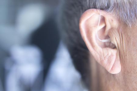 Foto de Modern digital in the ear hearing aid for deafness and the hard of hearing in aged man's ear. - Imagen libre de derechos