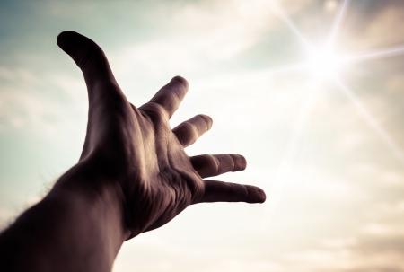 Photo pour Hand of a man reaching to towards sky  Color toned image   - image libre de droit