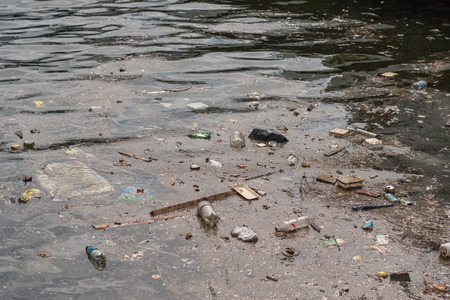 Foto de Oil and garbage pollution in the water. Selective focus with shallow depth of field. - Imagen libre de derechos