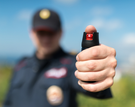 Photo for Detail of a police officer holding pepper spray. Selective focus with shallow depth of field. - Royalty Free Image