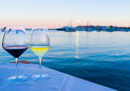 Foto de Glasses of wine with the view on the old town and port, Budva. - Imagen libre de derechos