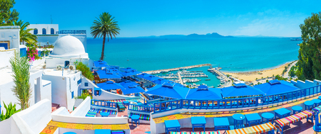 Foto de Sidi Bou Said boasts luxury restaurants and amazing viewpoints, overlooking its beaches, port and Cap Bon, seen on horizon, Tunisia. - Imagen libre de derechos