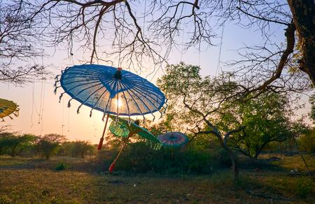 Foto de Romantic sunset in Bagan archaeological park with hanged burmese style umbrellas - Imagen libre de derechos