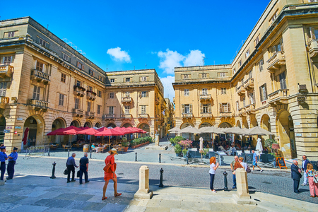 Foto de VALLETTA, MALTA - JUNE 17, 2018: The beautiful St John square, located in front of Co-Cathedral, with shady terraces of outdoor restaurants and stone arcades in monumental edifices, on June 17 in Valletta. - Imagen libre de derechos
