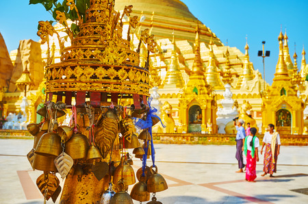 Foto de YANGON, MYANMAR - FEBRUARY 27, 2018: The close up of small hti umbrella with the ringing bells in front of the huge golden Shwedagon Pagoda, on February 27 in Yangon. - Imagen libre de derechos