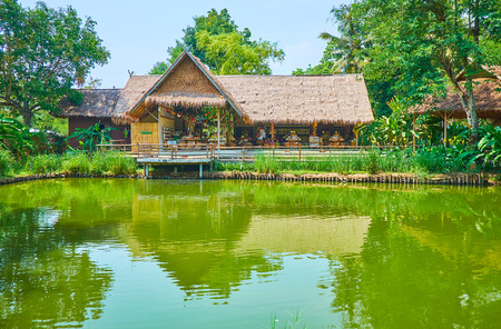 Photo pour CHIANG MAI, THAILAND - MAY 5, 2019: The scenic pond in Poopoopaper park with a view on nipa hut, housing the local souvenir store and cafe, on May 5 in Chiang Mai - image libre de droit