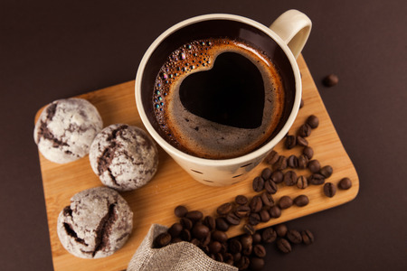 Photo for Cup of coffee with foam, heart shaped, with cookies and coffee beans, lying on the wooden stand, on brown background - Royalty Free Image