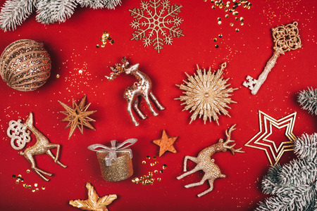 Photo for Christmas decorative toys: deers, stars, key, ball, present and glitter on red background. Flat lay style - Royalty Free Image