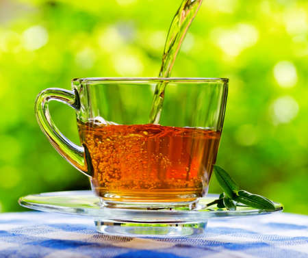 Foto de Invigorating fresh aromatic tea pouring into glass cup on the blue and white tablecloth in garden and on nature background. - Imagen libre de derechos