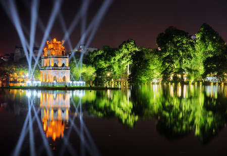 Photo for Night view of the Hoan Kiem Lake (Lake of the Returned Sword) and the Turtle Tower among blue light rays at historic centre of Hanoi in Vietnam. The tower reflected in the lake. - Royalty Free Image