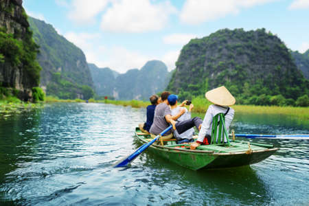 Foto de Tourists traveling in boat along the Ngo Dong River and taking picture of the Tam Coc, Ninh Binh, Vietnam. Rower using her feet to propel oars. Landscape formed by karst towers and rice fields. - Imagen libre de derechos