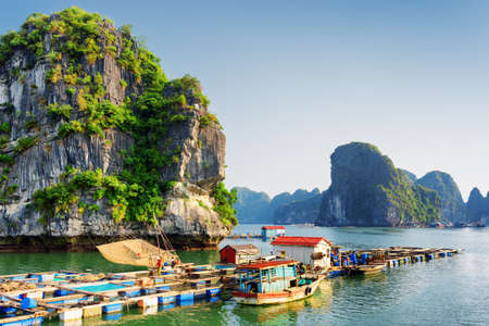 Foto de Floating fishing village in the Halong Bay (Descending Dragon) at the Gulf of Tonkin of the South China Sea, Vietnam. Landscape formed by karst towers-isles in various sizes. Blue sky in background. - Imagen libre de derechos