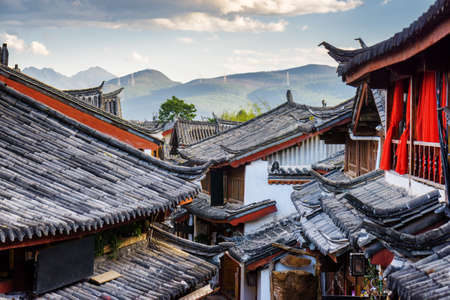 Photo for Scenic view of traditional Chinese tile roofs of houses in the Old Town of Lijiang, Yunnan province, China. Mountains in background. The Old Town of Lijiang is a popular tourist destination of Asia. - Royalty Free Image