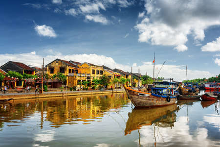 Photo for Wooden boats on the Thu Bon River in Hoi An Ancient Town (Hoian), Vietnam. Scenic yellow old houses on waterfront reflected in river. Hoi An is a popular tourist destination of Asia. - Royalty Free Image