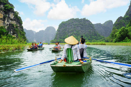 Foto de NINH BINH PROVINCE, VIETNAM - OCTOBER 14, 2015: Tourists traveling in boats along the Ngo Dong River at the Tam Coc portion. Rowers using their feet to propel oars. Landscape formed by karst towers. - Imagen libre de derechos