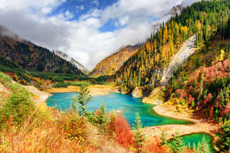 Photo for Fantastic view of the Upper Seasonal Lake with azure water among colorful fall woods and mountains in fog, Jiuzhaigou nature reserve (Jiuzhai Valley National Park), China. Sunny autumn landscape. - Royalty Free Image