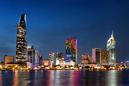 Photo pour Ho Chi Minh City skyline and the Saigon River. Amazing colorful night view of skyscraper and other modern buildings at downtown. Ho Chi Minh City is a popular tourist destination of Vietnam. - image libre de droit