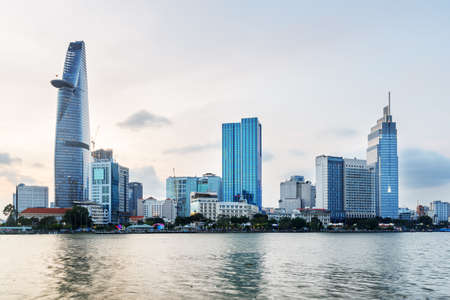 Foto de Ho Chi Minh City skyline and the Saigon River in Vietnam. Amazing evening view of skyscraper and other modern buildings at downtown. Beautiful cityscape. - Imagen libre de derechos