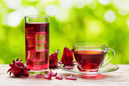Photo for Cup of magenta hot hibiscus tea (karkade, red sorrel, Agua de flor de Jamaica) and the same cold drink with ice in glass on nature background. Drink made from calyces (sepals) of roselle flowers. - Royalty Free Image