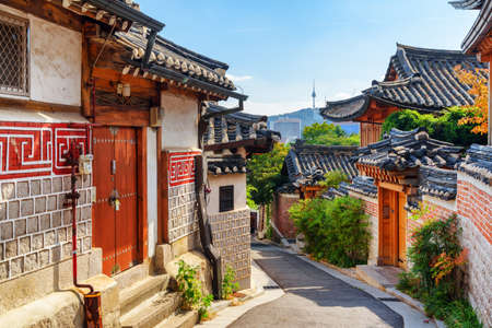 Foto de Awesome view of cozy old narrow street and traditional Korean houses of Bukchon Hanok Village in Seoul, South Korea. Seoul Tower on Namsan Mountain is visible on blue sky background. Scenic cityscape. - Imagen libre de derechos