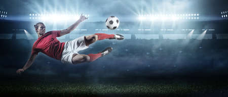 Soccer player in action on stadium background.The imaginary soccer stadium is modeled and rendered.