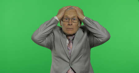 Foto de Elderly businessman. Desperate worried. Stressed shocked old senior man in formal wear holding head with hands on chroma key background. Place for your logo or text. Crisis in business concept - Imagen libre de derechos