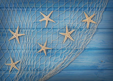 Foto de Seastars on the fishing net on a blue background - Imagen libre de derechos