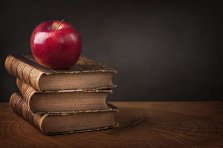 Photo for Stack of books and red apple on wooden table - Royalty Free Image