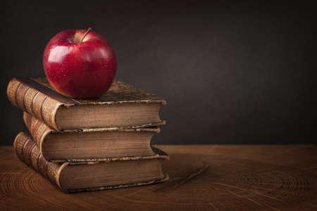 Foto de Stack of books and red apple on wooden table - Imagen libre de derechos