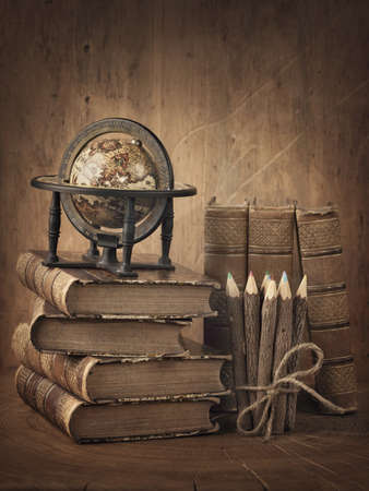 Foto de Stack of books and globe on wooden table - Imagen libre de derechos