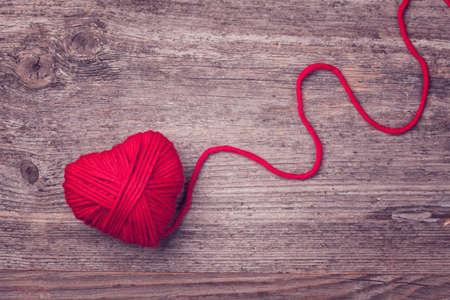 Foto de Red heart of red wool yarn on a wooden background - Imagen libre de derechos