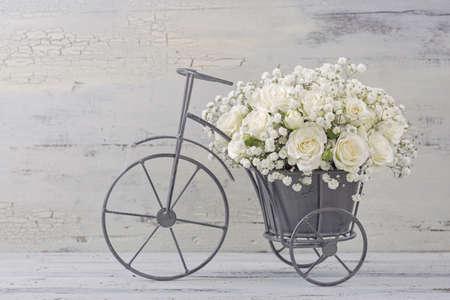 Photo pour White roses in a bicycle vase - image libre de droit