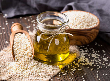 Photo for Sesame oil in glass and seeds - Royalty Free Image