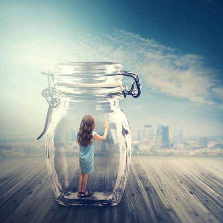 Foto de Young girl standing in a glass jar - Imagen libre de derechos