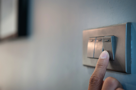 Foto de A finger is turning on a light switch. - Imagen libre de derechos