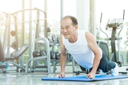 Foto de Asian senior man push up at the gym. copy space. - Imagen libre de derechos