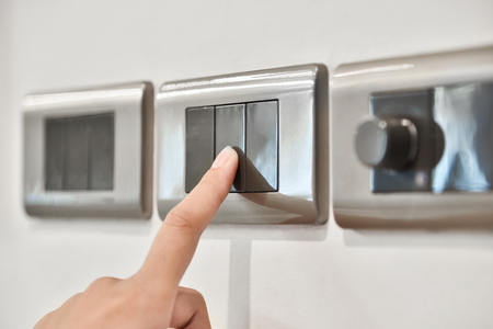 Foto de Close up hand turning on or off on grey light switches. Copy space. - Imagen libre de derechos