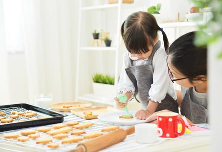 Foto de Asian Kid and young mother decorating cookies in the kitchen. - Imagen libre de derechos