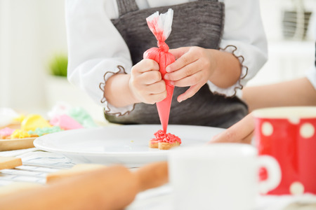 Foto de Close up on hands. Happy Asian Kid and young mother decorating cookies in the kitchen. - Imagen libre de derechos