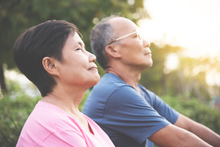 Photo for Happy Asian senior couple smiling and breathing fresh air while exercising at park outdoor. - Royalty Free Image