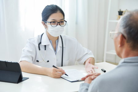 Photo pour Young Asian Female Doctor with protective mask talking to senior man patient in medical office. - image libre de droit