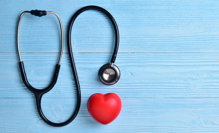 Foto de Red heart with stethoscope on blue wooden background. Copy space. Valentines day. - Imagen libre de derechos