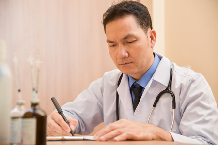 Photo pour Asian Senior male doctor is thinking about result of examination of his patients. Writing something on clipboard, prescription, paper work,patient check list paper or application form. - image libre de droit