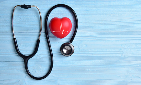 Photo pour Red heart with stethoscope on blue wooden background. Copy space. Valentines day. - image libre de droit