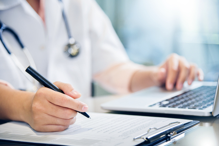 Photo pour Close up on hands. Asian female doctor is using laptop and writing something on clipboard, prescription, paperwork,patient checklist paper or application form at a hospital. - image libre de droit